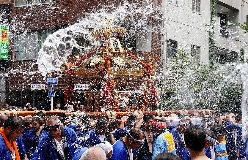 Spectators throwing water at the mikoshi carriers