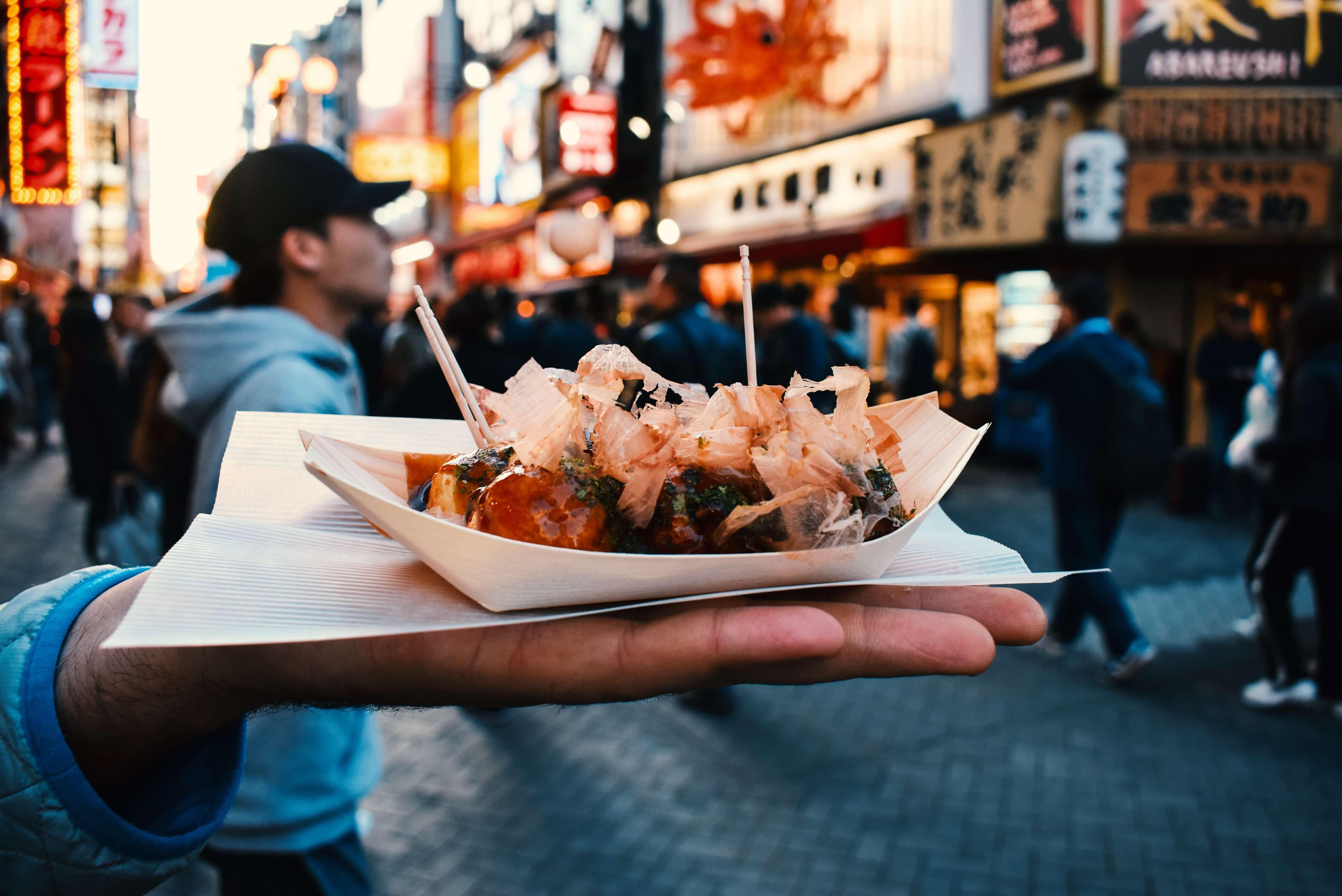 Eating takoyaki in Dotombori in Osaka